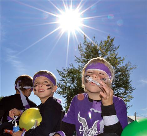 Below, Hayden Hollow, left, and Connor Nittinger ride their class float and fill the air with soap bubbles.a