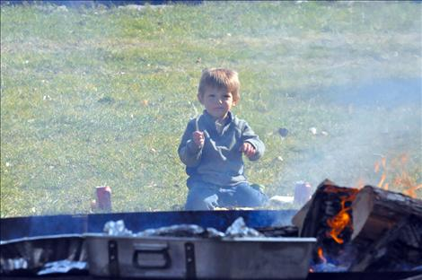 A boy eats in front of the fire at Bockman Park.
