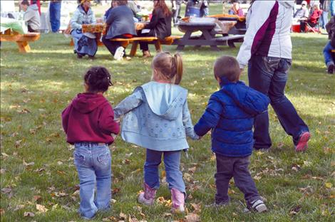 Maya St. Clair, Milee Cordier, and Xavier St. Clair hold hands at the Pig in the Park event.