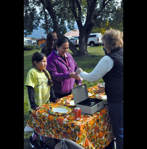 Ronna Walchuk takes donations and hands out plates at the pig in the park event.