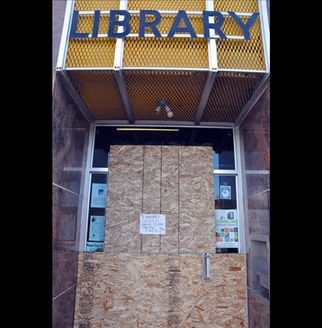 The Ronan Library was boarded up over the weekend after thieves threw a stone through the front door and stole the donation jar.
