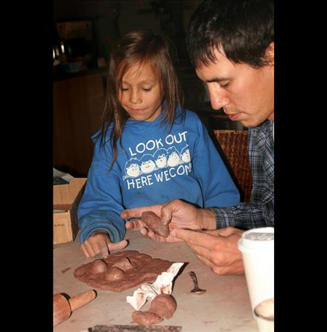 Bill Brown and Jayson, 5, work together tocreate a tile depicting a face.