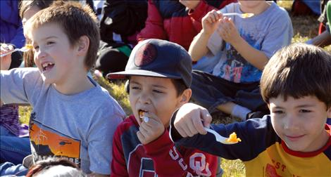 "Three Ronan second graders say ""Salut,"" before tasting their squash."