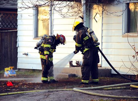 Polson firefighters hose off after saving a Polson home Monday, Nov. 11.