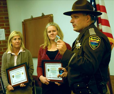 Megan Olsen and Jennifer Holt were honored by the Lake County Sheriff's Department for saving the life of a Missoula man last summer while vacationing at Lake Mary Ronan. Undersheriff Dan Yonkin helped present their awards.