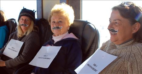The three mustacheketeers — Heather Davies, left, Pat Cook and Donna Steele — support the office mates.