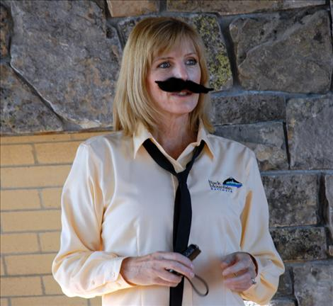 Darlis Smith sports a mustache as she emcees the Movember event at Black Mountain Software.
