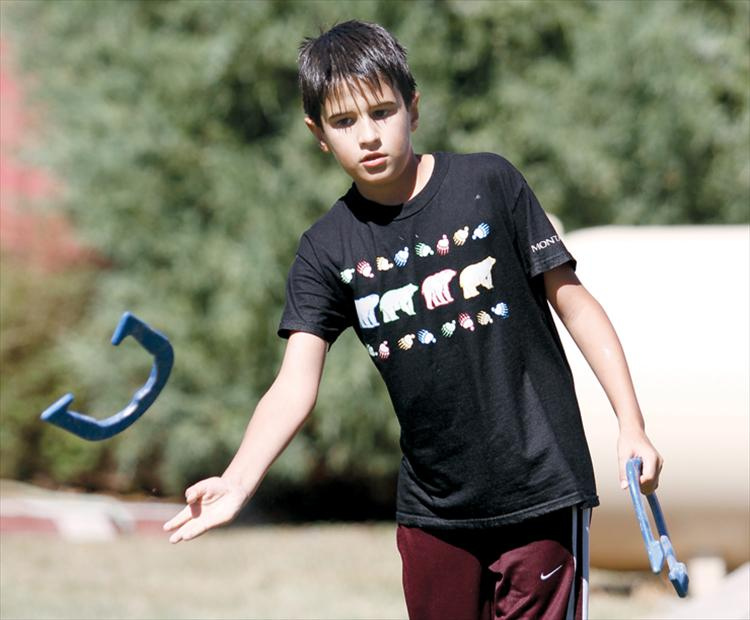 During a break from in Melon Days festivities, 10-year-old Reed Bocksnick of Ronan tosses a horseshoe with friends.
