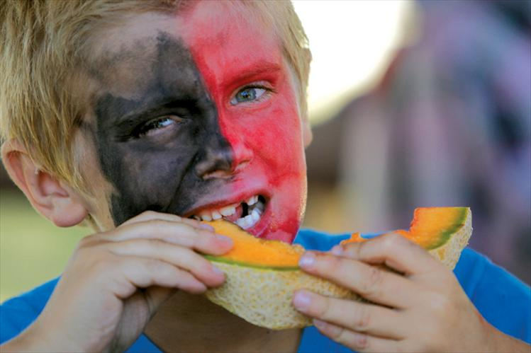 Stephen Ioli, a 7-year-old Dixon resident, chows down on a slice of Dixon melon during the melon-eating contest at Saturday's Dixon Melon Days.