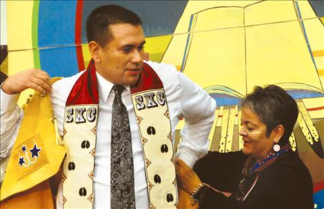 SKC President Robert DePoe III dons his new beaded buckskin vest with the help of JoJo Ducharme, member of the SKC Board of Directors. The board presented DePoe with the vest.