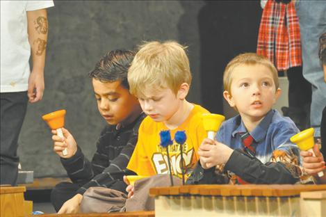 Students read music and follow instructions of teacher Tammy Krahn to know when to shake their bells in the Christmas Carol-Along.