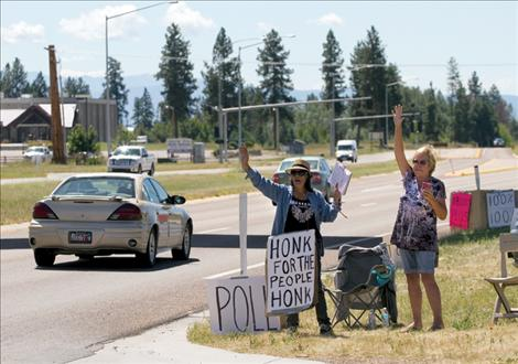 Members of the People's Voice, a group calling for the Confederated Salish and Kootenai Tribes to pay 100 percent of recently won settlement money to  individual tribal members, wave to passers-by in Pablo near CSKT  headquarters earlier this month.