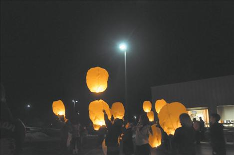 A crowd of people light lanterns before they are sent to the heavens bearing messages for loved ones.