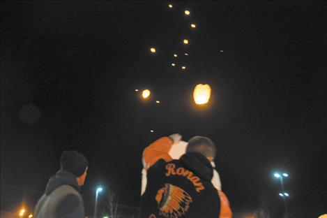 A Ronan Student Council member holds a latern as others form an upward trail of floating beacons in honor of people separated from their families by distance or death this holiday season.