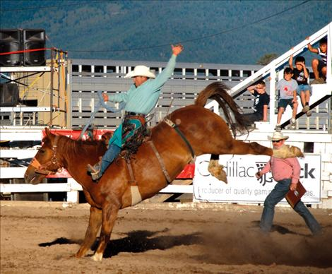 Saddle bronc rider Marty Hebb exhibits classic saddle bronc style as he spurs a big sorrel bronc.