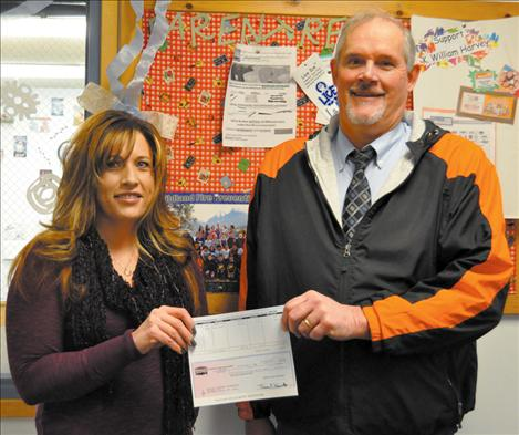 Town Pump District Manager Leslie Goss delivers a $500 check to K.William Harvey Elementary School Principal Ted Madden.