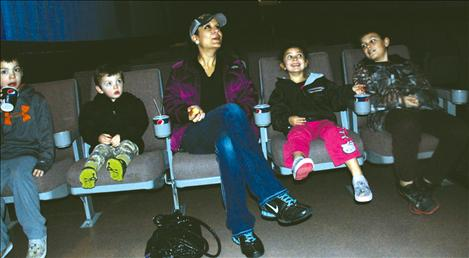 "A family, with cups of juice and cereal bars, wait for ""Despicable Me 2"" to begin on Jan. 25."