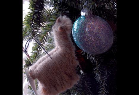 Miniature alpaca Christmas ornaments adorn a tree.