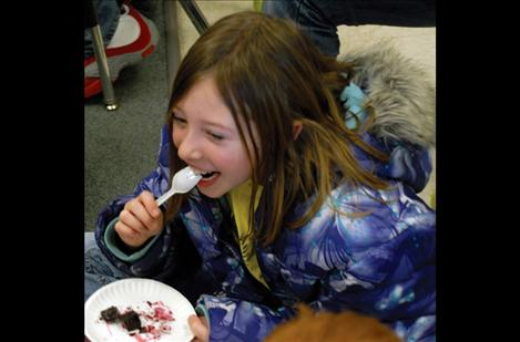 Fourth grader Mattison Holmes laughs with a classmate as she eats her beets.