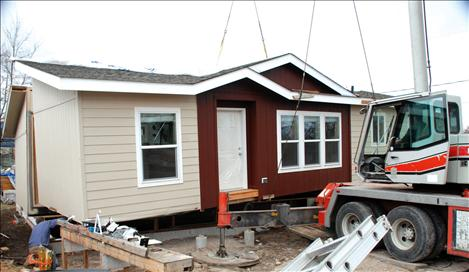 A crane drops half of Lucky and Barbara Donegan's house into place in Polson.
