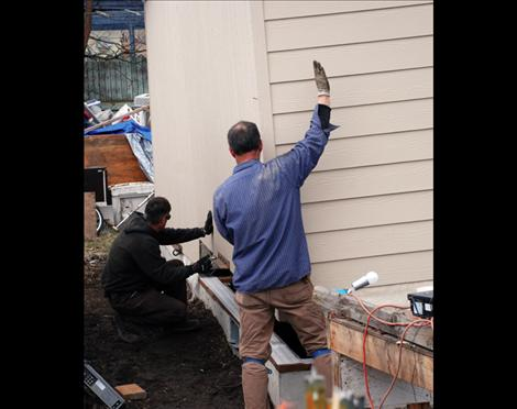 Workers lower Lucky and Barbara Donegan's house into place in Polson.