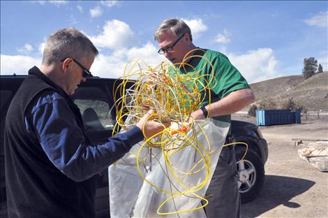 Lake County Solid Waste Manager Mark Nelson and Lake County Emergency Operations Director Steve Stanley place blasting caps into a garbage bag so proper disposal measures can be taken.