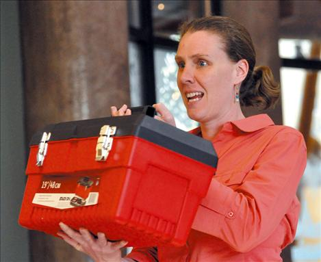 Heidi Sedivy shows the Flathead Basin Commission a speaker's toolbox of visual aids that can be used to educate the public about invasive species.
