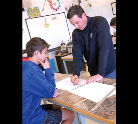 PHS art teacher Matt Holmes explains perspective to student Thunder Morales in art class.