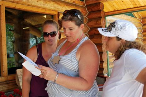 Bobbi Stammers Justine Welker, and Kelly Morigeau observe a scavenger hunt clue found at Ninepipes Lodge on Saturday.