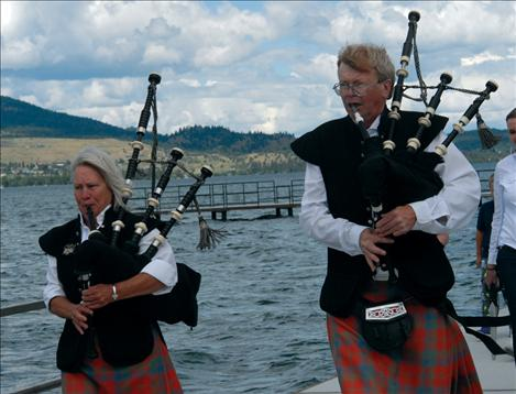 Bagpipers Dick Bratton and Sandy Farrell lead people through the new city dock.