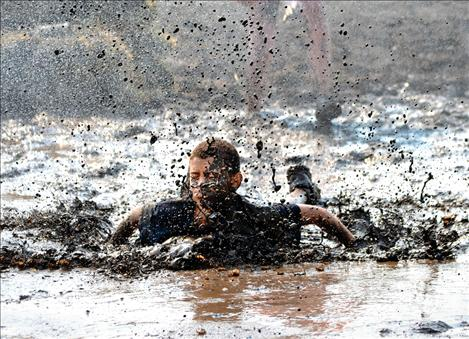 Isaiah Silgen finishes the Boys and Girls Mud Run obstacle course Saturday morning with a belly flop into the mucky mud pit.