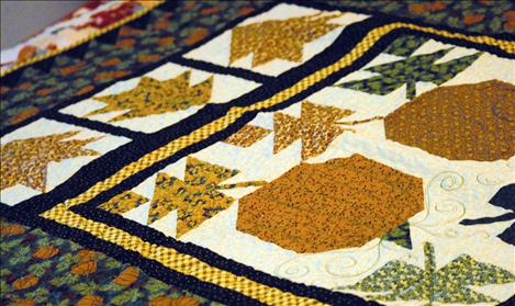 A Thimbleberries quilt, featuring pumpkins, yellows, greens and blues is one of at least 80 quilts in Pat Anderson's house.