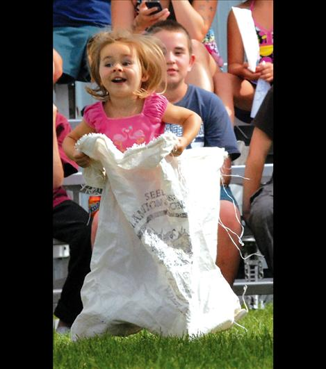 Katherine Bartel, 3, bounces her way through the sack races sponsored by the Lions Club July 30.