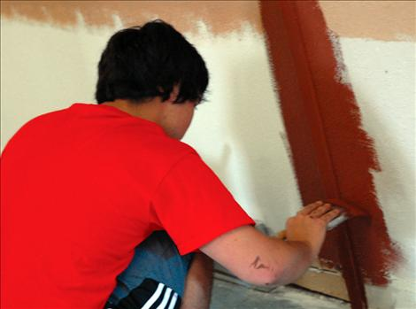 Workmen begin plastering, painting and trimming the halls and room
