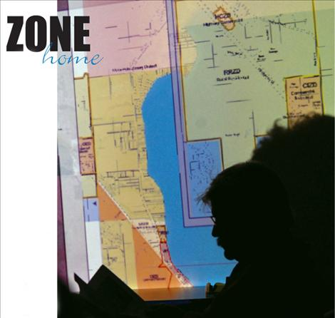 Residents attending the city/county planning board meeting study handouts and a map of Polson zoning districts.