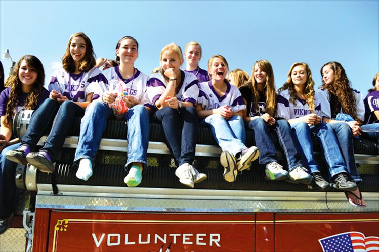 The Charlo volleyball team rides atop a fire truck in Friday's homecoming parade.