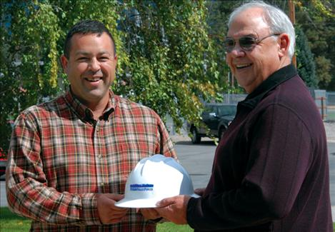 Ralph Goode, right, hands overs his Mission Valley Power hardhat to Jean Matt.