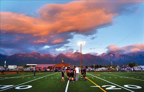 The Ronan Chiefs huddle up Friday evening on their own turf in front of the scenic Mission Mountains.