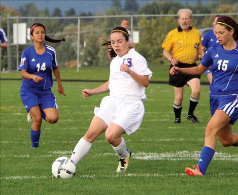 Two-time All-State recipient Sarah Howell craftily sneaks by opponents at Thursday's Homecoming game against Bigfork.