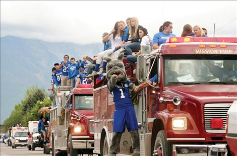 Mission High School football players parade through St. Ignatius Friday afternoon, a day before their homecoming game.