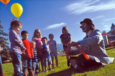 Children watch as a balloon is magically transformed into a dog by a clown at the Ronan Harvest Fest.