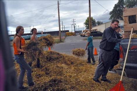 Noah Cheff, Ashtin Courville, Cori Normandeau, Veyanna Curley, and Principal Curt Schutzmann shovel up hay that was left scattered after young vandals caused $8,500 worth of damage at Ronan Power Products.