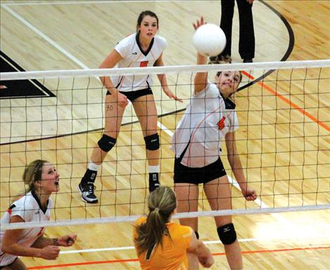 Ashley Peterson and McKenzie Dulmes jump for a block.