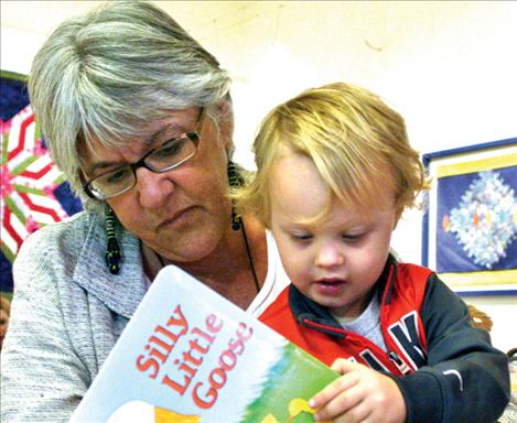 Karen Peterson photo Family support specialist Jen Blumberg from Lake County Public Health reading to two-year-old Braxtyn Chadwick.