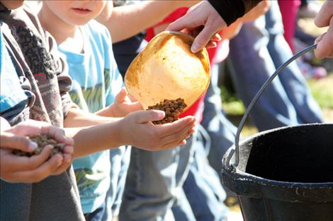 Valley View students are each given a handful of food to feed to the fish at the Arlee hatchery.
