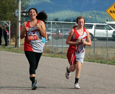 Scarlet Naomi Plant gives an enthusiastic thumbs up while pacing teammate Alice North at Hatchery Challenge Invite