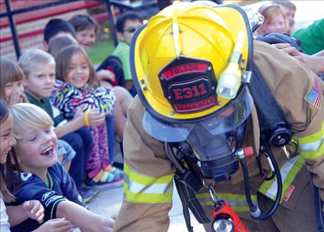 Second grade students at Linderman Elementary School try to attract Polson Firefighter Tanner Hayes' attention.