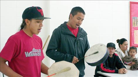 Zach Felsman, 18, and Kyle Felsman, 22, sing a traditional song before folks line up for fry bread.