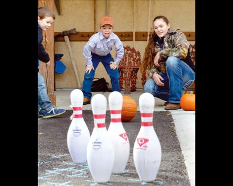 Levi Conover, 7, watches to see if the pumpkin goes in the right direction to knock over his pins.