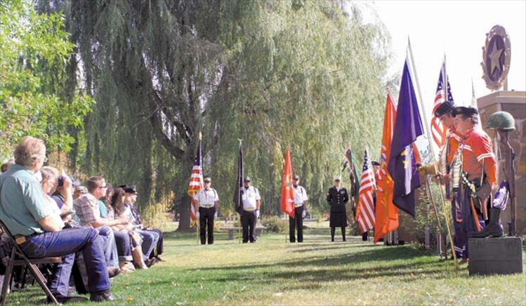 Gold Star mothers and their families (left) listen to a speech as Mission Valley Honor Guard members (Center) and CSKT Veteran Warriors Society members (right) stand guard over the memorial in Ronan's city park.